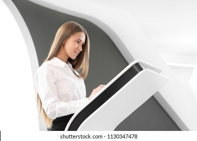 Young beautiful girl uses a touch screen computer terminal on a white background.