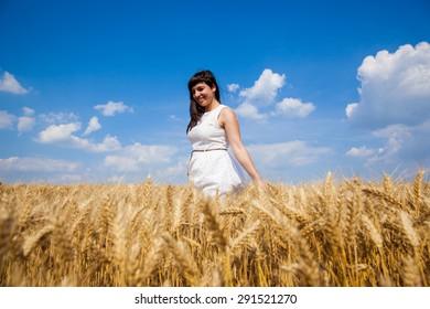 Young beautiful girl walk through golden field of wheat and enjoy life