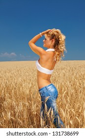 Young and beautiful girl walking through wheat field on sunny summer day