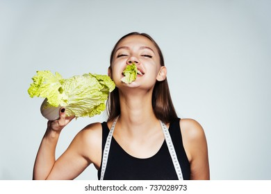 a young beautiful girl wants to lose weight, eats a healthy low-calorie Peking cabbage