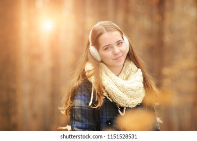 Young beautiful girl with warm scarf and earmuffs looking up in the autumn forest with blurred background and sunlight