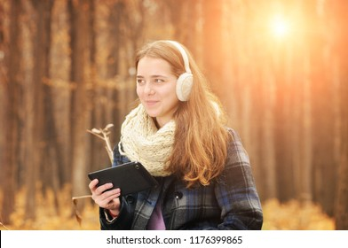 Young beautiful girl with warm scarf and earmuffs holding black tablet in the autumn forest with blurred background with sunlight
