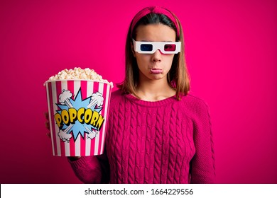 Young beautiful girl watching movie using 3d glasses eating box with popcorns depressed and worry for distress, crying angry and afraid. Sad expression.