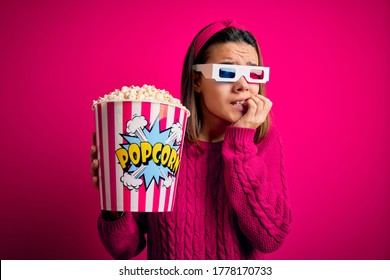 Young beautiful girl watching movie using 3d glasses eating box with popcorns looking stressed and nervous with hands on mouth biting nails. Anxiety problem.