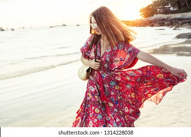 Young beautiful girl wearing boho maxi dress walking on sand. Summer fashion clothes for the beach.