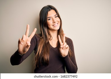Young beautiful girl wearing casual sweater standing over isolated white background smiling looking to the camera showing fingers doing victory sign. Number two.