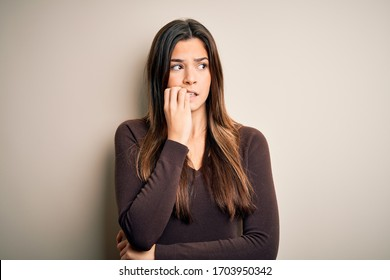 Young beautiful girl wearing casual sweater standing over isolated white background looking stressed and nervous with hands on mouth biting nails. Anxiety problem.