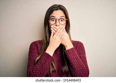 Young beautiful girl wearing casual sweater and glasses over isolated white background shocked covering mouth with hands for mistake. Secret concept.