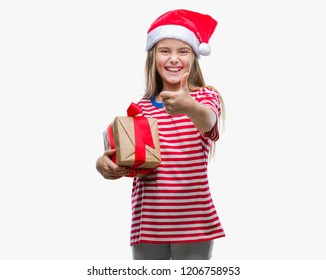 89f0c189bbdc3 Young beautiful girl wearing christmas hat and holding gift over isolated  background happy with big smile