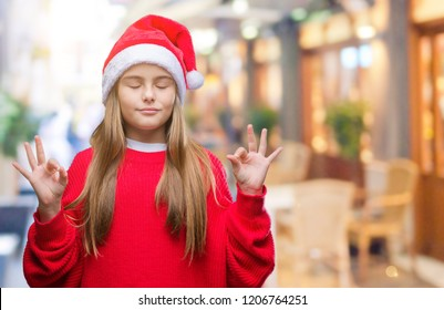 Young beautiful girl wearing christmas hat over isolated background relax and smiling with eyes closed doing meditation gesture with fingers. Yoga concept.