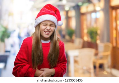 Young beautiful girl wearing christmas hat over isolated background with hand on stomach because indigestion, painful illness feeling unwell. Ache concept.