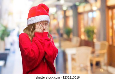 Young beautiful girl wearing christmas hat over isolated background with sad expression covering face with hands while crying. Depression concept.