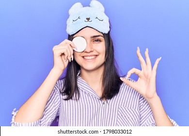Young beautiful girl wearing funny sleep mask using makeup remover cotton doing ok sign with fingers, smiling friendly gesturing excellent symbol
