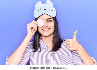 Young beautiful girl wearing funny sleep mask using makeup remover cotton smiling happy and positive, thumb up doing excellent and approval sign
