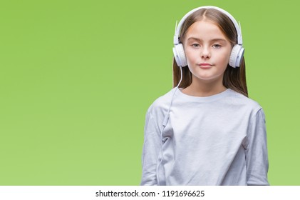 Young beautiful girl wearing headphones listening to music over isolated background with serious expression on face. Simple and natural looking at the camera.