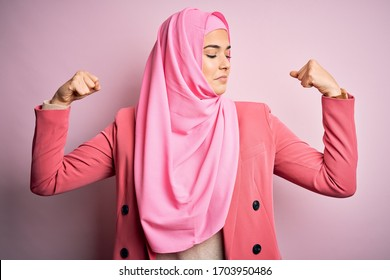 Young beautiful girl wearing muslim hijab standing over isolated pink background showing arms muscles smiling proud. Fitness concept.
