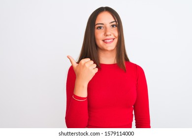 Young beautiful girl wearing red casual t-shirt standing over isolated white background smiling with happy face looking and pointing to the side with thumb up.