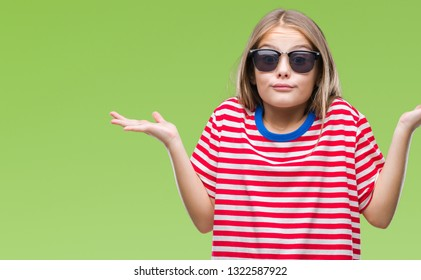Young beautiful girl wearing sunglasses over isolated background clueless and confused expression with arms and hands raised. Doubt concept.