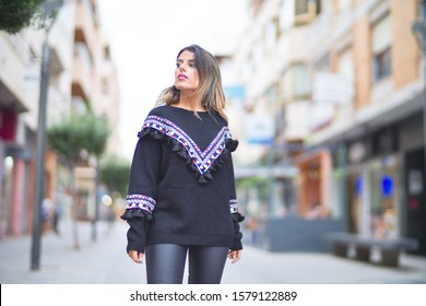 Young beautiful girl wearing sweater walking at street town