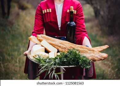 Young beautiful girl wearing traditional georgian dress holds a tray full of traditional georgian food: cheese, bread, greens and wine.