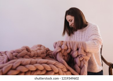Young beautiful girl wearing warm rosy sweater knitting with pink wool big merino warm blanket. Rosy tender natural yarn. Cold winter. Cozy, comfortable, soft rug