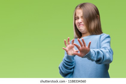 Young beautiful girl wearing winter sweater over isolated background disgusted expression, displeased and fearful doing disgust face because aversion reaction. With hands raised. Annoying concept.