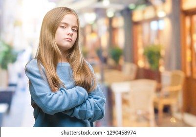 Young beautiful girl wearing winter sweater over isolated background skeptic and nervous, disapproving expression on face with crossed arms. Negative person.