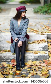 Young beautiful girl wearing winter coat and cap sitting on steps full of autumn leaves Lifestyle and fashion concept.