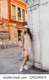 young beautiful girl in a white dress walks through the streets of Venice in Italy
