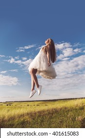 Young beautiful girl in a white dress flying over a field of wheat on a sunny day