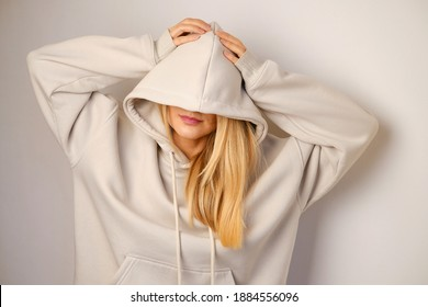 Young beautiful girl in a white hoodie posing. Warm oversized hoodie with an hood. Stylish trendy hipster bow. Trying on clothes in a store. Youth subculture. Fashion clothing advertising - Shutterstock ID 1884556096