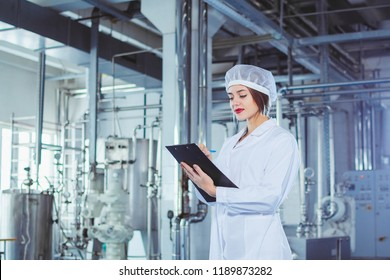 A young beautiful girl in white overalls makes notes in a tablet on the background of equipment of a food processing plant. Quality control in production.