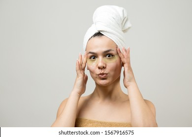 Young beautiful girl in a white towel on his head wears collagen gel patches under her eyes. Mask under eyes treatment face.