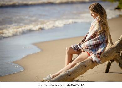Young beautiful girl woman enjoying sunset at stormy sea