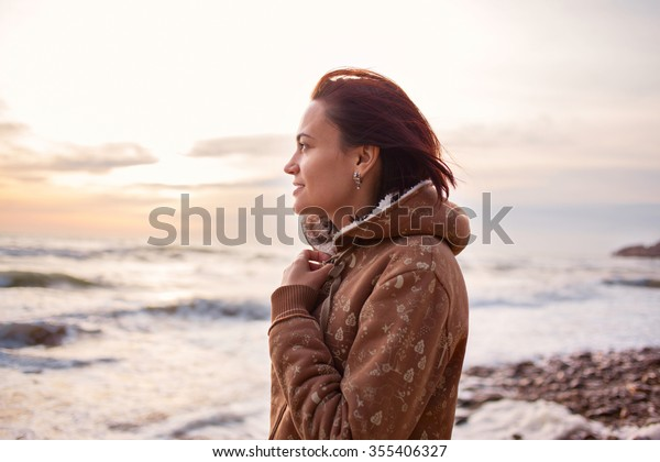Young beautiful girl woman enjoying sunset at stormy sea in winter