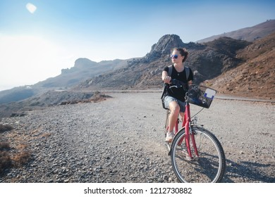 Young beautiful girl woman travels by bicycle on a mountain landscape on the beach in the sun, tourism and leisure concept, Greece, Kos