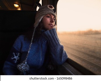 Young beautiful girl with a woolen hat and a jumper travels by train looking through the window towards the shining golden morning light