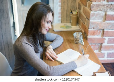 Young Beautiful girl working at home: writing in her notebook, using laptop, texting with smatrphone and just resting sitting on window sill. The workday of a freelance editor.