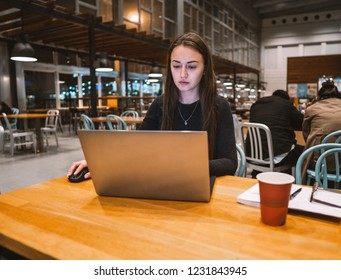 Young, beautiful girl working with laptop and drinking coffee at a wooden table in an empty airport terminal cafe