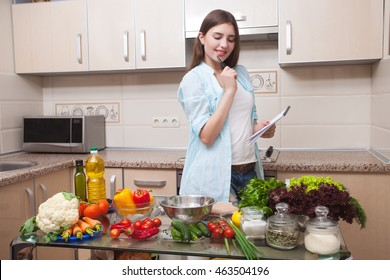 Young beautiful girl writes recipe diet salad in the kitchen . A healthy way of life . Home kitchen