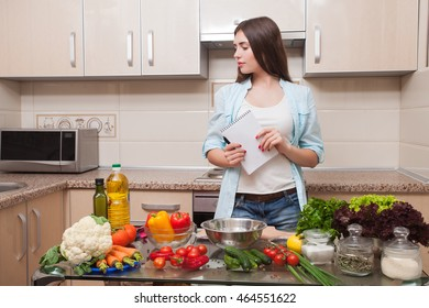 Young and beautiful girl writes a salad recipe