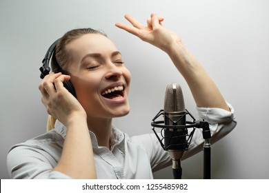 Young beautiful girl writes vocals, radio, voiceover tv, reads poetry, blog, podcast in studio on studio microphone in headphones on white background