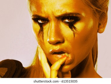 Young beautiful girl in yellow light with a crying make-up holds a finger in her mouth