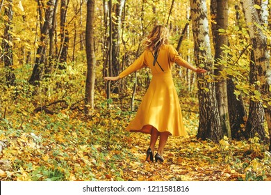 Young beautiful girl in a yellow long dress walks in autumn park with fallen leaves