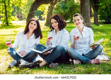 Young beautiful girls with glass of red wine and books in the park. Nature background