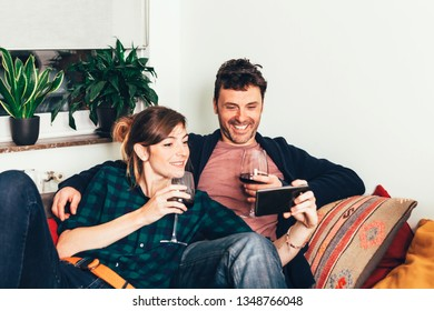 a young beautiful good looking couple relaxing with wine and mobile phone