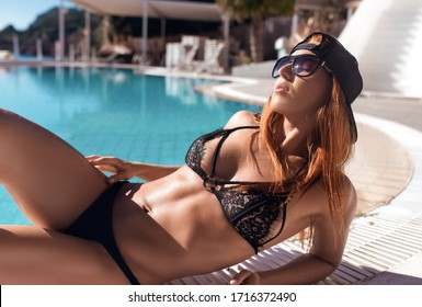 Young beautiful gorgeous fit bikini model pose at Corfu Greece lying next to swimming pool