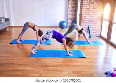 Young beautiful group of sportswomen practicing yoga doing downward-facing dog pose at gym