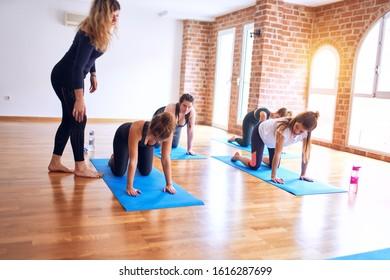 Young beautiful group of sportswomen practicing yoga. Coach teaching downward-facing dog to sporty women at gym