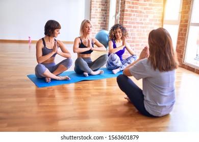 Young beautiful group of sportswomen sitting on mat practicing yoga. Coach teaching lotus pose at gym